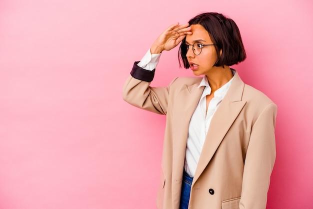 Junge business-mixed-race-frau isoliert auf rosa hintergrund, die weit weg schaut und die hand auf die stirn hält.