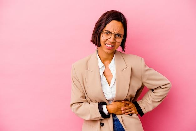 Junge business-mixed-race-frau isoliert auf rosa hintergrund mit leberschmerzen, bauchschmerzen.