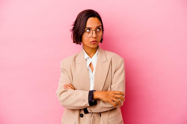 Junge business-mixed-race-frau isoliert auf rosa hintergrund müde von einer sich wiederholenden aufgabe.