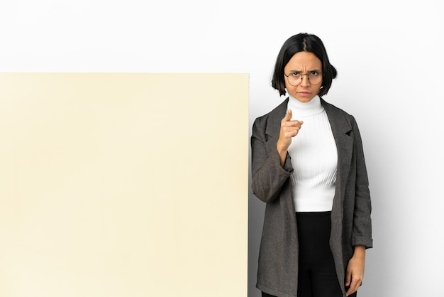 Junge business-mixed-race-frau mit einem großen banner isolierten hintergrund frustriert und zeigt nach vorne