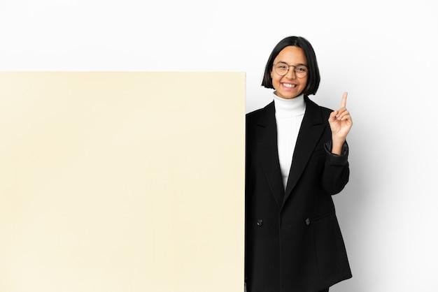 Junge business-mixed-race-frau mit einem großen banner über isoliertem hintergrund, das auf eine großartige idee hinweist