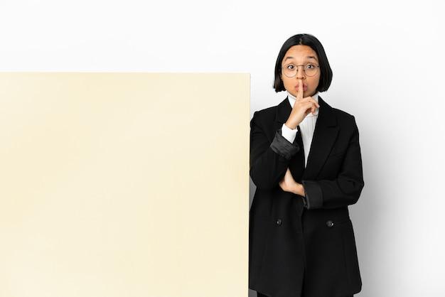 Junge business-mixed-race-frau mit einem großen banner über isoliertem hintergrund, das ein zeichen der stille zeigt, geste, die finger in den mund steckt