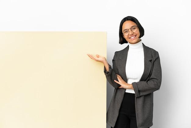 Junge business-mixed-race-frau mit einem großen banner über isoliertem hintergrund, der imaginäre kopien auf der handfläche hält, um eine anzeige einzufügen