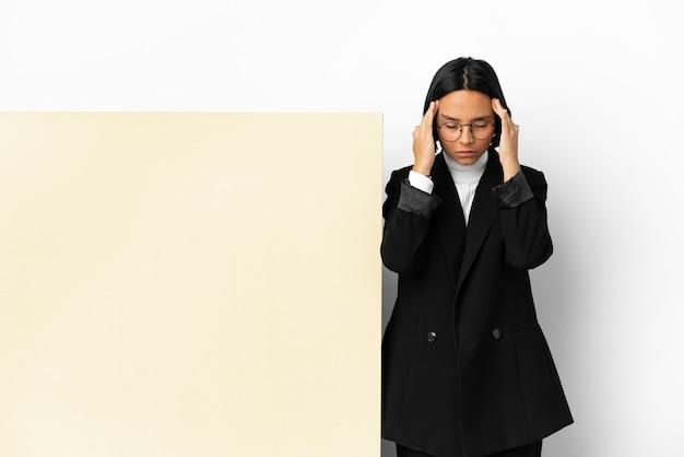 Junge business-mixed-race-frau mit einem großen banner über isoliertem hintergrund mit kopfschmerzen