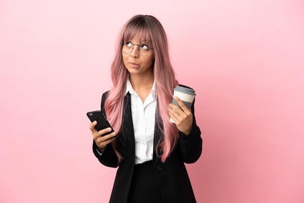 Junge business-mixed-race-frau mit rosa haaren isoliert auf rosa hintergrund, die kaffee zum mitnehmen und ein handy hält, während sie etwas denkt