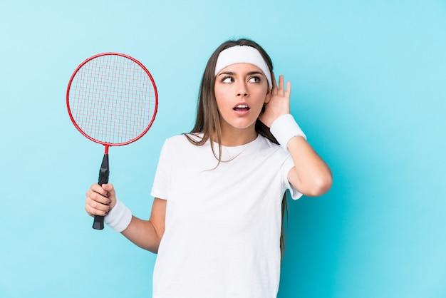 Junge caucasic frau, die das badminton versucht, einen klatsch zu hören spielt.