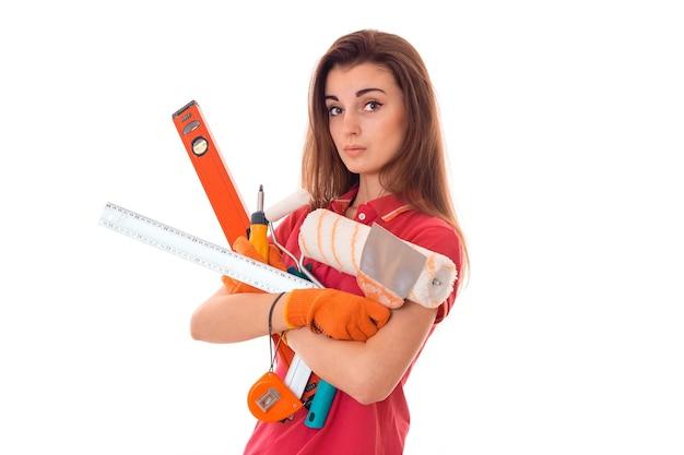 Junge charmante baumeisterin in uniform mit vielen werkzeugen macht renovierung isoliert auf weißer wand