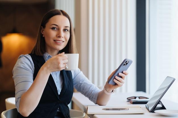 Junge charmante frau, die mit smartphone eine sms schreibt, während sie allein im kaffeegeschäft sitzt, das kaffee trinkt, gespräch mit handy hat
