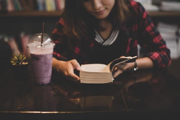 Junge charmante frau mit milchshake und lesung buch sitzt innen im café. casual porträt von teenager-mädchen.