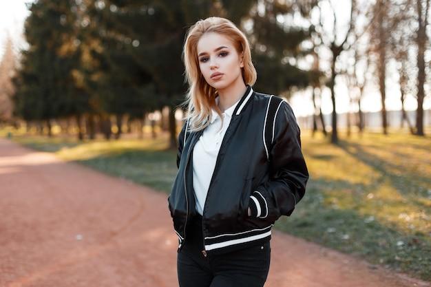Junge charmante fraublondine mit schönen augen in einem modischen weißen hemd in einer stilvollen hellschwarzen jacke auf bäumen und sonnenuntergang im park. stilvolles mädchenmodell. amerikanischer stil
