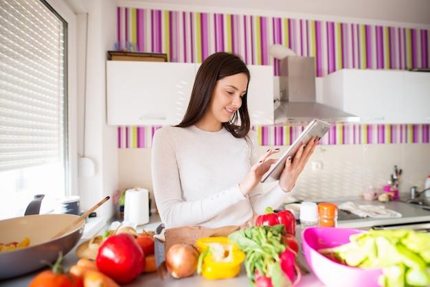 Junge charmante freudige frau benutzt ihre tablette, während sie vor einer hellen küchentheke steht, die mit frischem gemüse gefüllt ist.