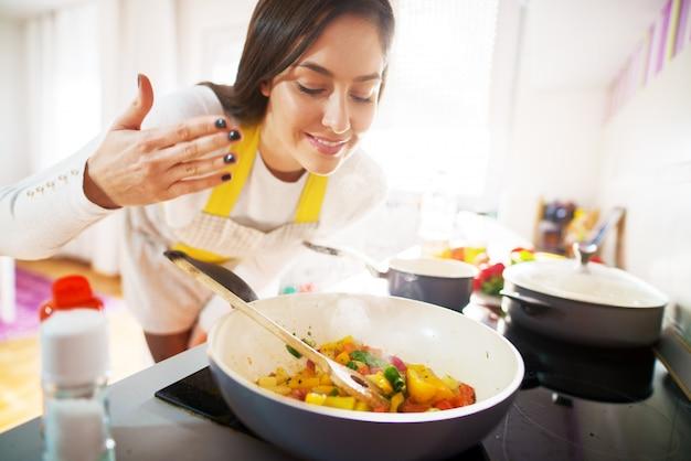 Junge charmante hübsche frau lächelt, während sie das aroma ihres frischen gesunden frühstücks riecht, das gekocht wird.