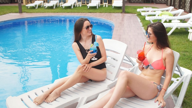 Junge charmante mädchen genießen cocktails, die auf den ganders in der nähe des pools ruhen.