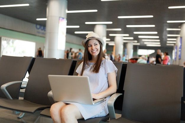 Junge charmante reisende touristenfrau mit hut, die am laptop arbeitet, während sie in der lobbyhalle am internationalen flughafen wartet?