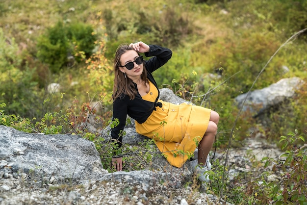 Junge charmefrau auf einem stein, der in den sommerferien in der landschaft genießt