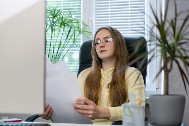 Junge chefin überprüft mitarbeiterberichte. vertragsstudium vor der unterzeichnung.