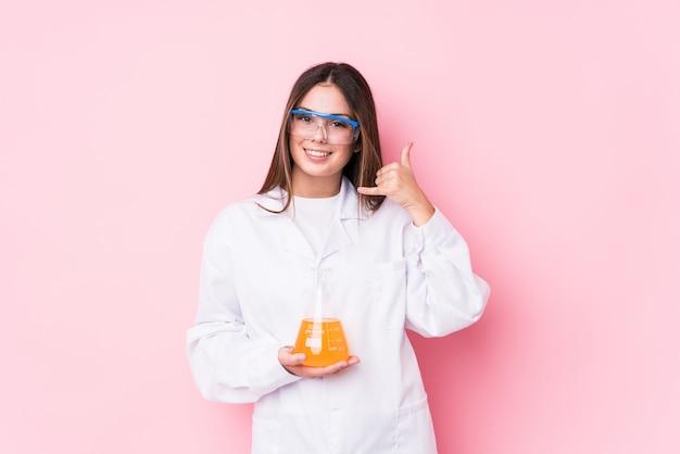 Junge chemische frau, die eine handy-anrufgeste mit den fingern zeigt