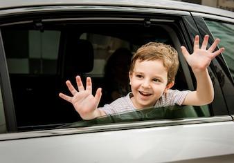 Junge CHild im Auto-freundlichen lächelnden Gruß