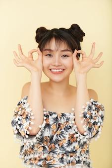 Junge chinesin, die im studio mit lustigen handzeichen aufwirft