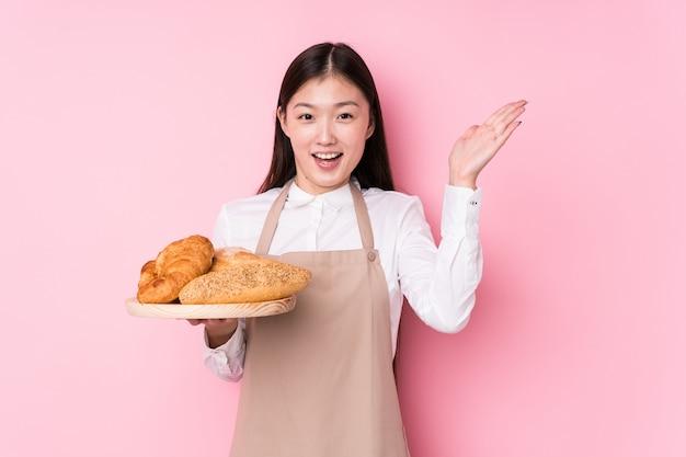 Junge chinesische bäckerfrau lokalisiert, eine angenehme überraschung empfangend, aufgeregt und hände anhebend.