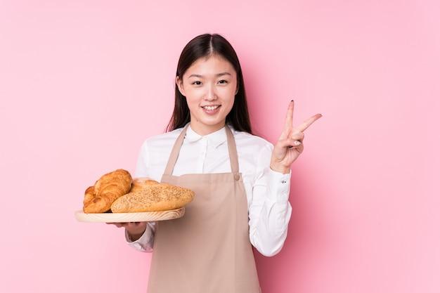 Junge chinesische bäckerin, die nummer zwei mit den fingern zeigt.