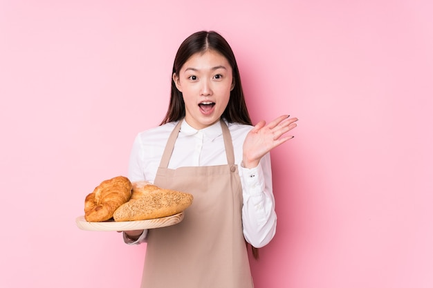 Junge chinesische bäckerin isoliert überrascht und schockiert.