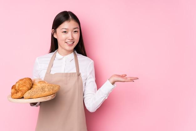 Junge chinesische bäckerin lokalisiert, die einen kopienraum auf einer handfläche zeigt und eine andere hand auf taille hält.