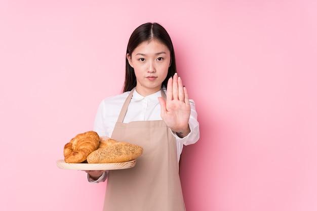 Junge chinesische bäckerin lokalisiert stehend mit ausgestreckter hand, die stoppschild zeigt, das sie verhindert.