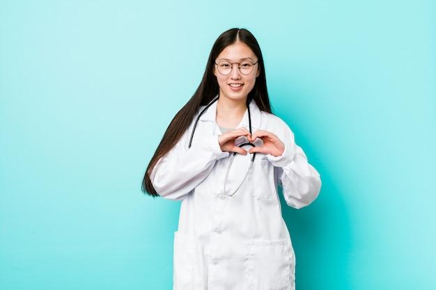 Junge chinesische doktorfrau, die eine herzform mit den händen lächelt und zeigt.