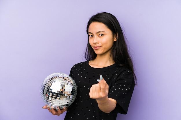 Junge chinesische frau auf einer lila wand, die discokugel hält