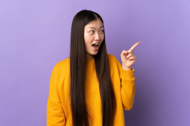 Junge chinesische frau auf isoliertem purpur, das beabsichtigt, die lösung zu realisieren, während ein finger angehoben wird
