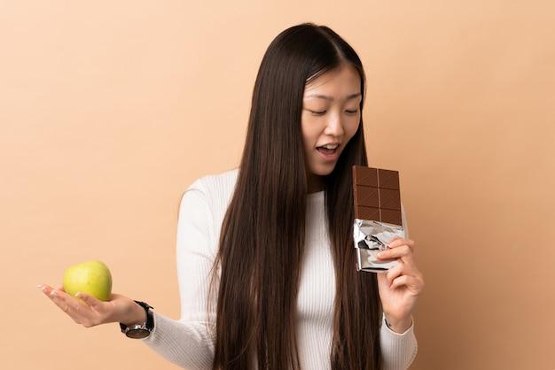 Junge chinesische frau auf lokalisiertem nehmen einer schokoladentafel in einer hand und eines apfels in der anderen