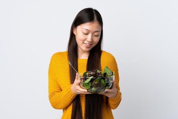Junge chinesische frau auf lokalisiertem weiß, das eine schüssel salat mit glücklichem ausdruck hält