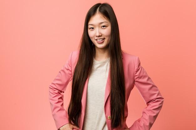 Junge chinesische frau des geschäfts, die den rosa anzug überzeugt trägt, hände auf ihm hüften halten.