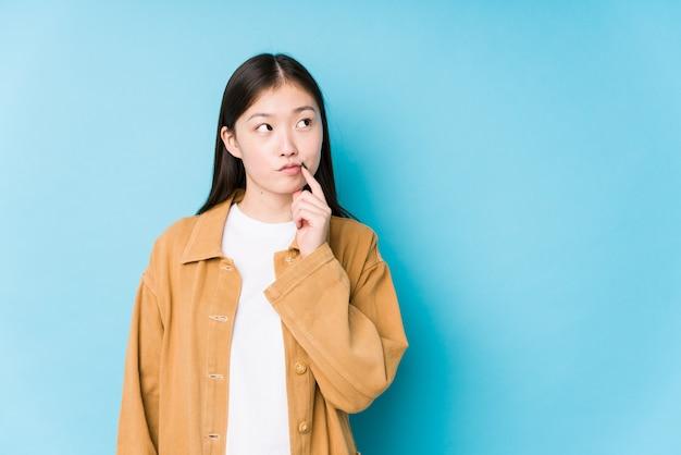 Junge chinesische frau, die auf blauem isoliertem blick seitwärts mit zweifelhaftem und skeptischem ausdruck aufwirft.