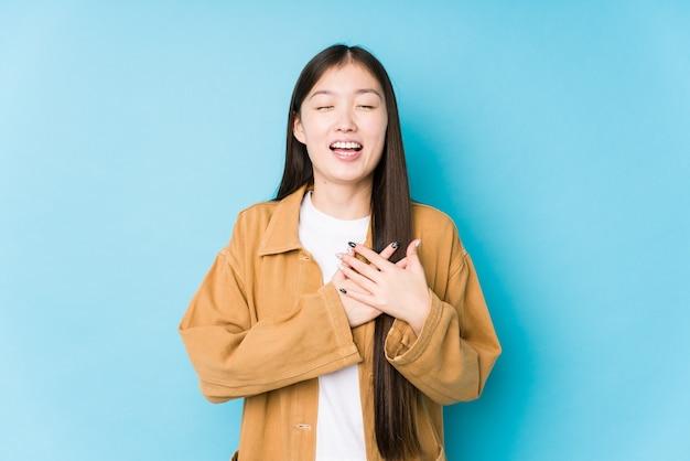 Junge chinesische frau, die auf blauem isoliertem lachen posiert, das hände auf herz hält, konzept des glücks.