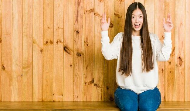 Junge chinesische frau, die auf einem hölzernen platz empfängt eine angenehme überraschung, aufgeregt und hände anhebt sitzt.