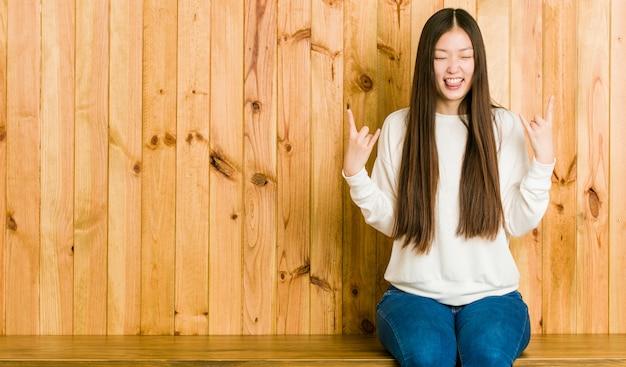 Junge chinesische frau, die auf einem hölzernen platz sitzt, der felsengeste mit den fingern zeigt