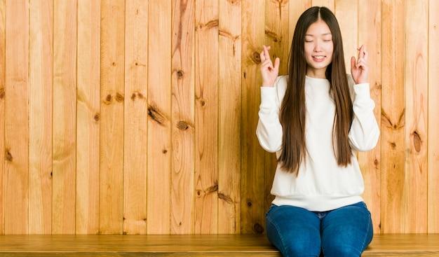 Junge chinesische frau, die auf einem hölzernen platz sitzt, der finger für glück kreuzt