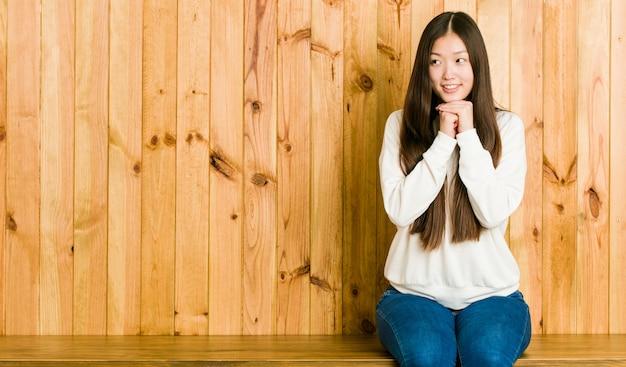 Junge chinesische frau, die auf einem hölzernen platz sitzt, hält hände unter kinn, schaut glücklich beiseite.