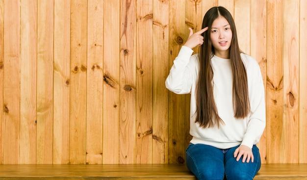 Junge chinesische frau, die auf einem hölzernen platz zeigt eine enttäuschungsgeste mit dem zeigefinger sitzt.
