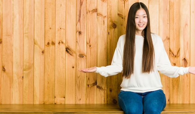 Junge chinesische frau, die auf einem hölzernen platz zeigt einen willkommenen ausdruck sitzt.