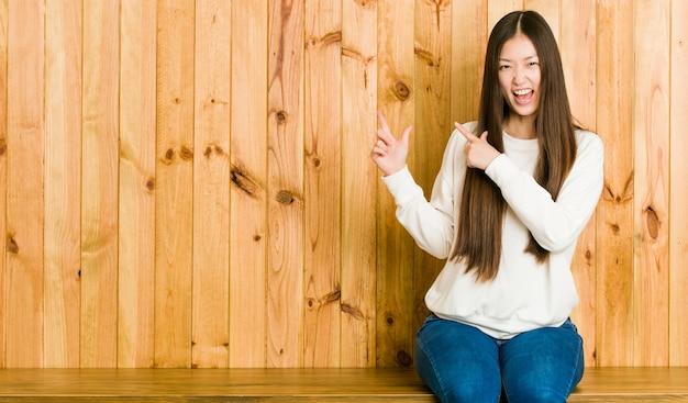 Junge chinesische frau, die auf einem hölzernen platz zeigt mit den zeigefingern auf a, aufregung und wunsch ausdrückend sitzt.