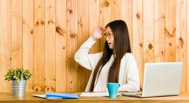 Junge chinesische frau, die auf ihrem schreibtisch schaut weit weg studiert, hand auf stirn halten.