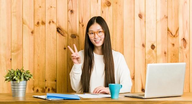 Junge chinesische frau, die auf ihrem schreibtisch zeigt siegeszeichen studiert und breit lächelt.