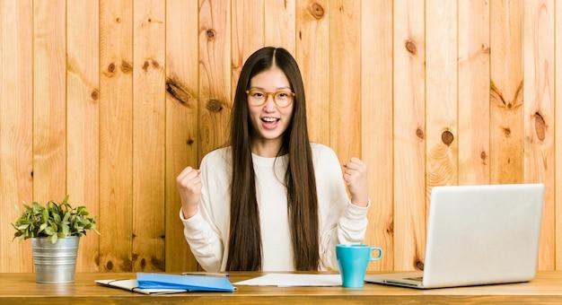 Junge chinesische frau, die auf ihrem schreibtisch zujubelt sorglos und aufgeregt studiert. sieg-konzept.