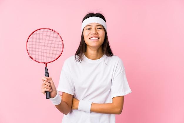 Junge chinesische frau, die badminton in einer rosa wand spielt, die lacht und spaß hat.