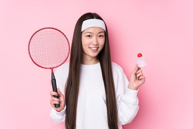 Junge chinesische frau, die badminton spielt, isoliert glücklich, lächelnd und fröhlich.