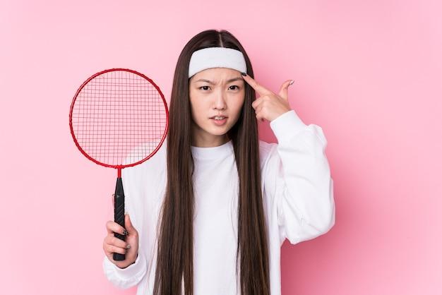 Junge chinesische frau, die badminton spielt, isoliert zeigt eine enttäuschungsgeste mit zeigefinger.