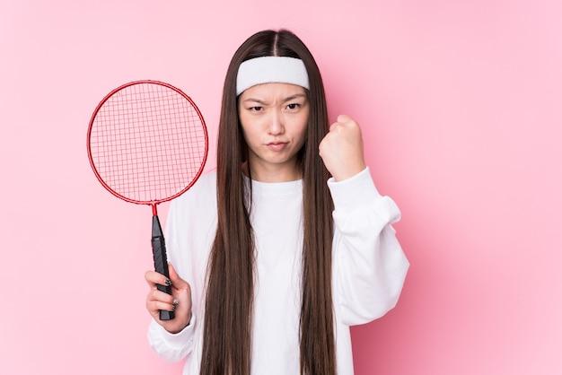 Junge chinesische frau, die badminton spielt, isoliert zeigt faust, aggressiven gesichtsausdruck.